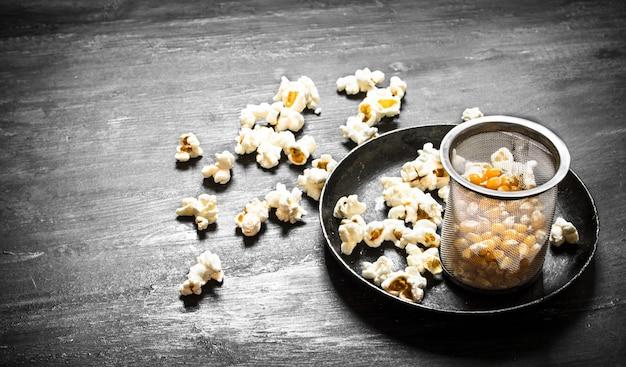 Popcorn mit mais in der schale auf holztisch.