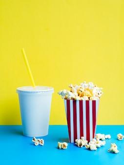 Popcorn mit soda auf buntem hintergrund
