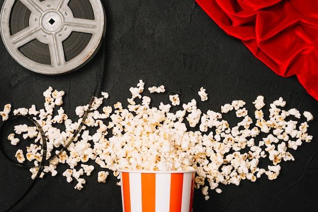 Popcorn nahe filmrolle und rotem tuch