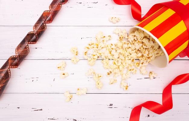 Popcorn, rotes band auf weißem hölzernem hintergrund. valentinstag, kino.