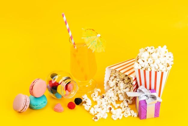Popcorn und cocktail von vorne mit französischen macarons und confitures auf gelb