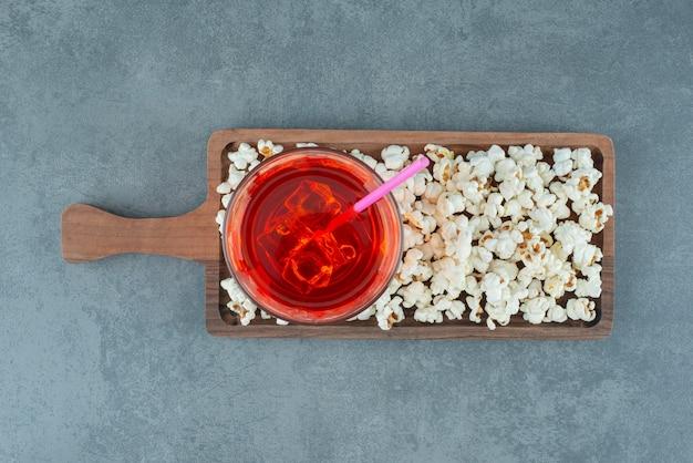 Popcorn und ein glas eisiges getränk auf einem holzbrett auf blauem hintergrund. foto in hoher qualität