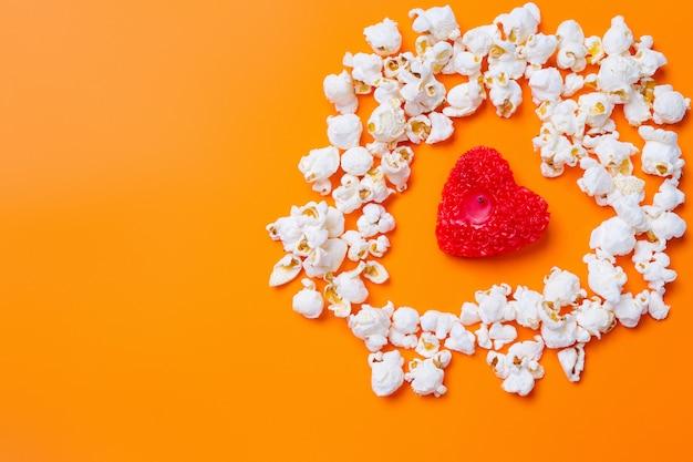 Popcorn und eine kerze in der form eines roten herzens auf orange hintergrund mit leerzeichen.