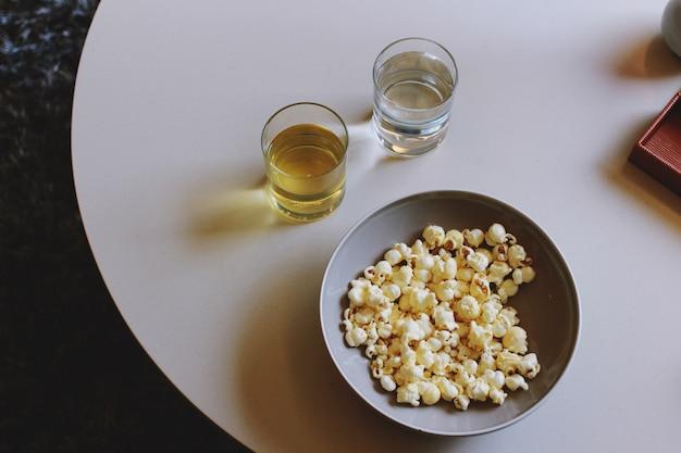 Popcorn und glas wasser und alkoholfreies getränk auf weißem schreibtisch für snack-zeit