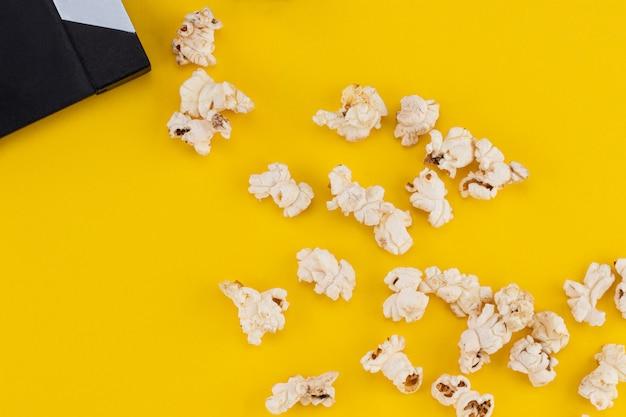 Popcorn und klappe auf buntem hintergrund. draufsicht