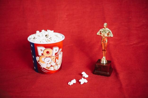 Popcorn und oscar-statuette auf rotem stoff