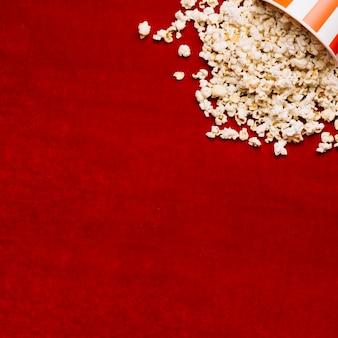 Popcorn verschüttete aus eimer auf rotem tuch