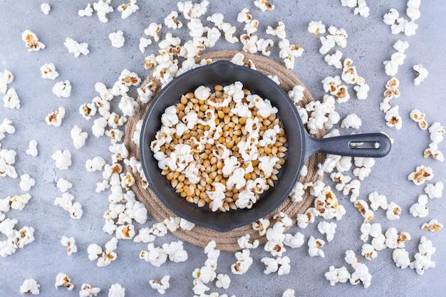 Popcorn verstreut um eine pfanne mit maiskörnern auf marmoroberfläche