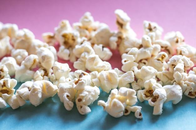Popcornkino auf rosa pastell und blauem pastellhintergrund. film-snack