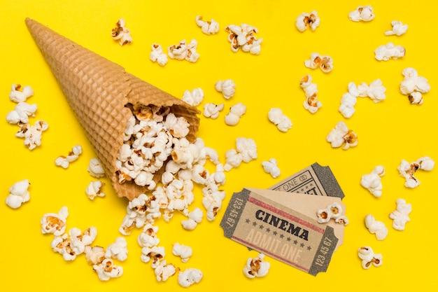 Popcorns, die den waffelkegel mit kinokarten gegen gelben hintergrund überlaufen