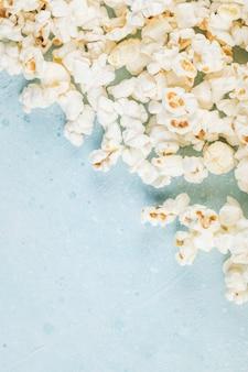 Popcorns verteilen sich auf dem blauen tisch aus der rechten ecke