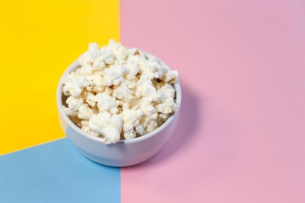 Popcornschüssel auf gelbem, rosa und blauem hintergrund. heimkino, freunde planen