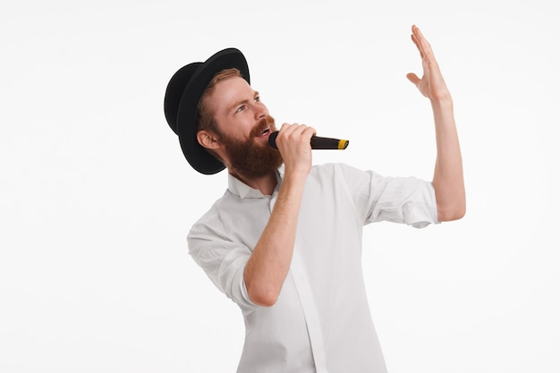 Popsänger mit fuzzy-bart, der emotional gestikuliert, während er mit dem mikrofon auftritt. attraktiver bärtiger junger männlicher animateur, der schwarzen hut und weißes hemd hält mikrofon hält und etwas ankündigt