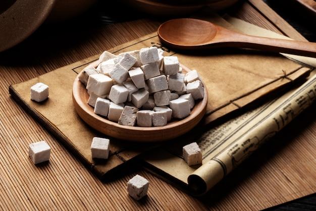 Poria cocos, alte chinesische medizinbücher und kräuter auf dem tisch