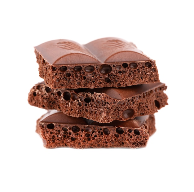 Poröse schokoladenstücke lokalisiert auf weißem hintergrund. schwarze kohlensäurehaltige schokolade.