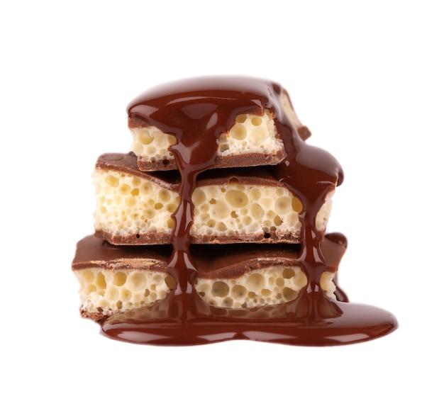 Poröse schokoladenstücke und schokoladensirup, lokalisiert auf weißem hintergrund. weiße kohlensäurehaltige schokolade.