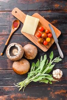 Portabello pilze zutaten zum backen, cheddar-käse, kirschtomaten und salbei auf alten dunklen tisch, draufsicht.