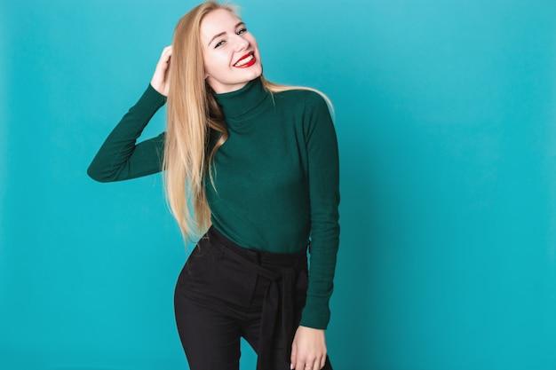 Portait von frohen blondinen, die auf einem blauen hintergrund stehen