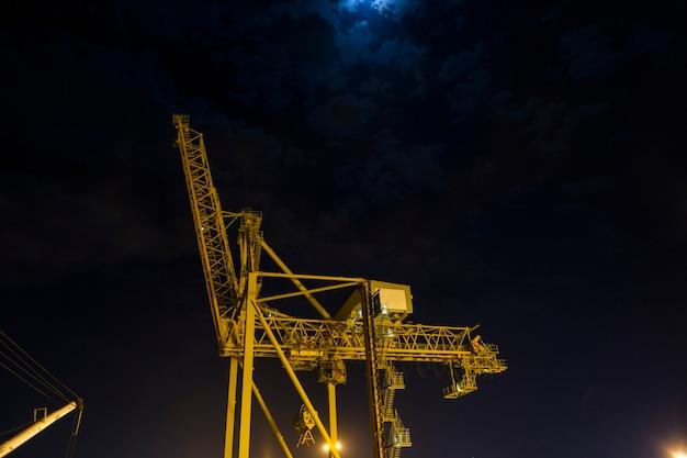 Portalkran im hafen nachts. gelber kran und dunkler himmel.