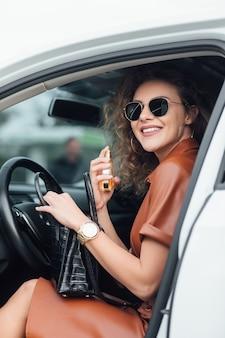Portarit der geschäftsfrau mit ihrem parfüm im auto