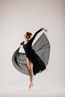 Portarit des sinnlichen professionellen kaukasischen callet-tänzers im bodysuit und in den spitzenschuhen auf weiß.