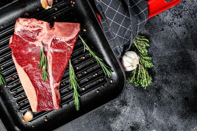 Porterhouse rohes steak. bio-fleisch rindfleisch. schwarzer raum. draufsicht. speicherplatz kopieren.