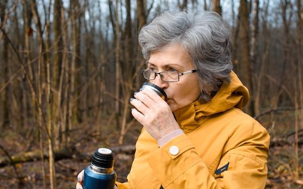 Portert ältere frau in gläsern, die heißen tee, nahaufnahme trinken. ältere frau, die im wald geht. erwärmendes getränkekonzept bei kaltem wetter, aktiver ruhestandslebensstil.