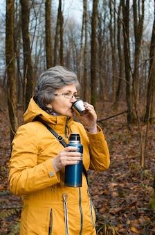 Portert ältere frau in gläsern, die heißen tee trinken. ältere frau, die im wald geht. erwärmendes getränkekonzept bei kaltem wetter, aktiver ruhestandslebensstil.