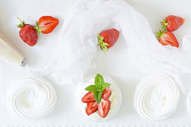 Portion australisches dessert pavlova mit luftiger buttercreme, frischen erdbeeren und minze auf einem weißen teller.