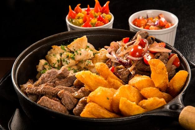 Portion fleisch mit pommes und gebratener yucca, zwiebel mit gemüse und paprika