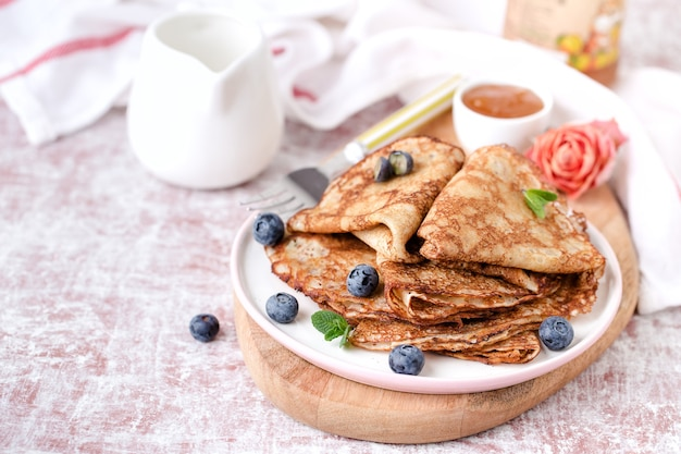 Portion gebratene pfannkuchen mit honig und blaubeeren in einem teller auf einem holzbrett auf dem tisch.