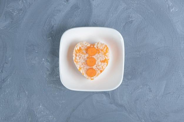 Portion gekochter reis neben einem handtuch auf marmortisch.