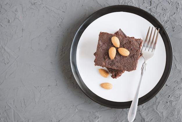 Portion hausgemachter schokoladenbrownie mit mandelnüssen