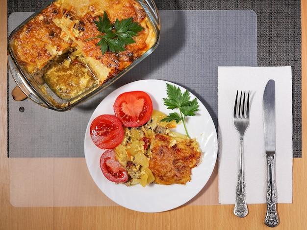 Portion kartoffelauflauf mit fleisch auf teller mit frischen tomaten Premium Fotos
