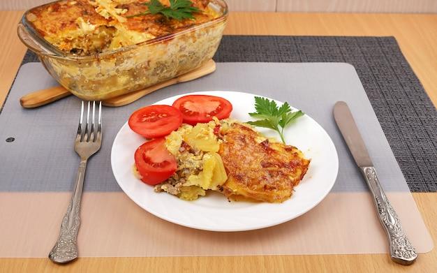 Portion kartoffelauflauf mit fleisch, goldene kruste auf teller mit frischen tomaten auf dem tisch