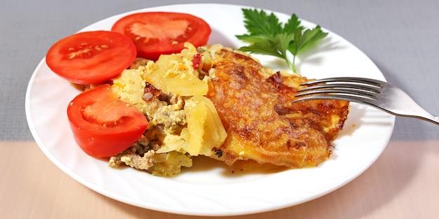 Portion kartoffelauflauf mit goldener fleischkruste auf teller mit frischen tomaten Premium Fotos