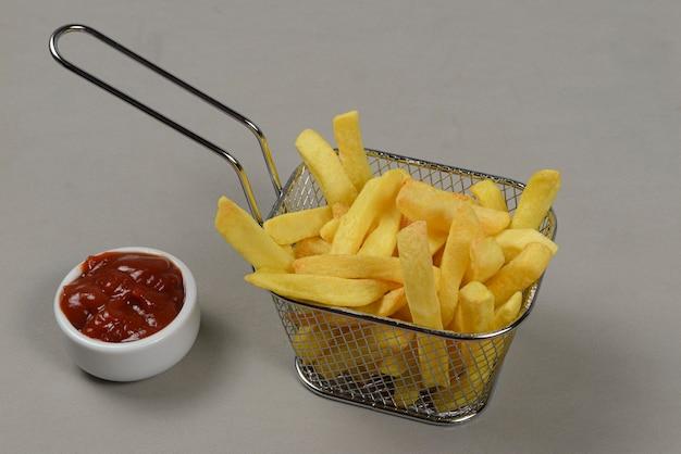 Portion kartoffelchips in einem metallkorb in einer neutralen oberfläche