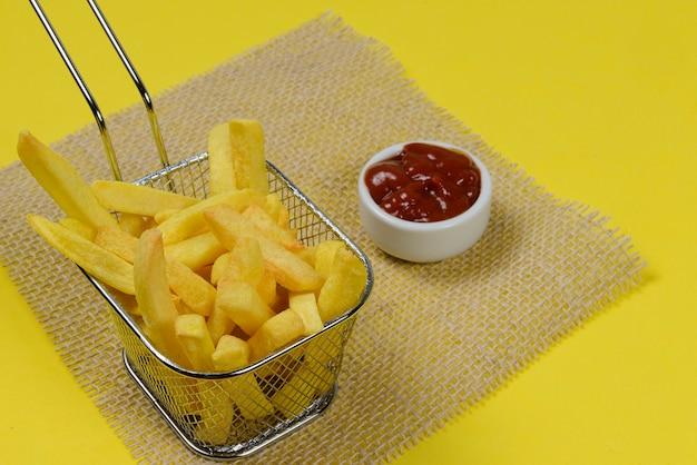 Portion kartoffelchips in einem metallkorb.