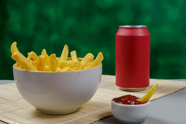 Portion kartoffelpommes in einer schüssel mit soda und ketchup