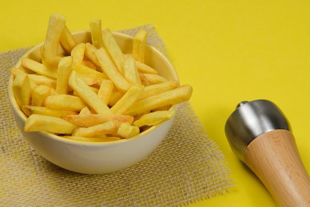 Portion kartoffelpommes in keramikschale auf gelb