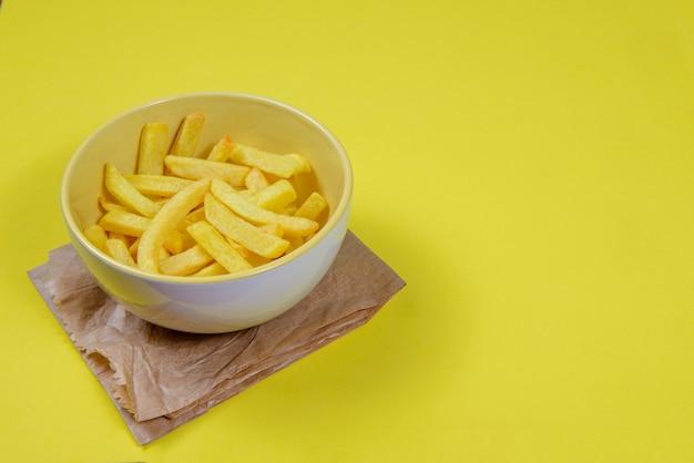 Portion kartoffelpommes in keramikschale auf lokalem gelbem hintergrund