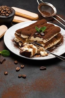 Portion klassisches tiramisu-dessert und savoiardi-kekse auf betonhintergrund