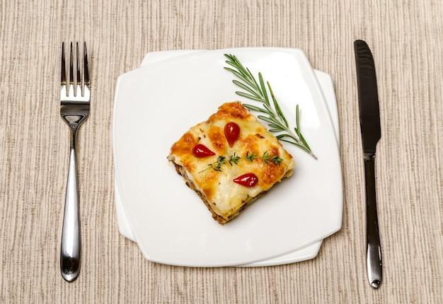 Portion lasagne auf dem holztisch