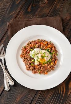 Portion pochierte eier mit hackfleisch