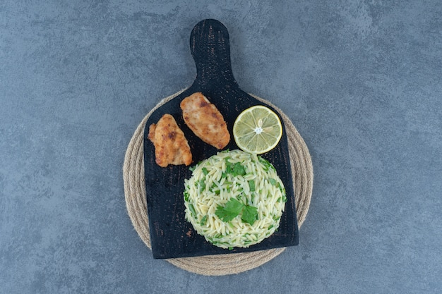 Portion reis mit chicken nuggets auf schwarzem brett.
