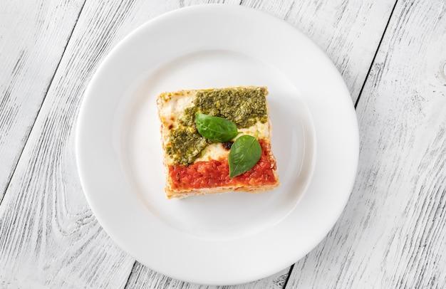 Portion ricotta-lasagne mit tomatensauce und pesto