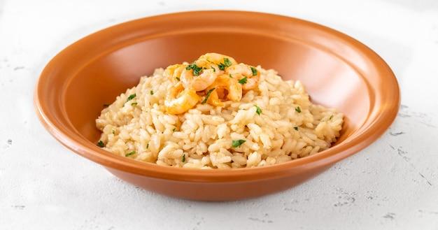 Portion risotto mit garnele in der schüssel garniert