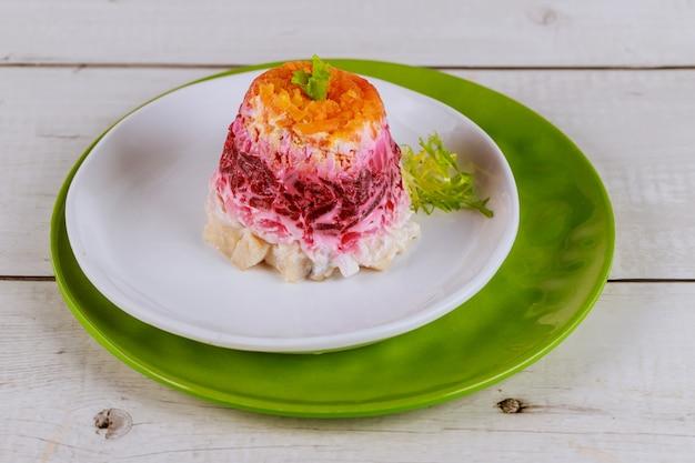 Portion rote-bete-salat mit hering und gemüse