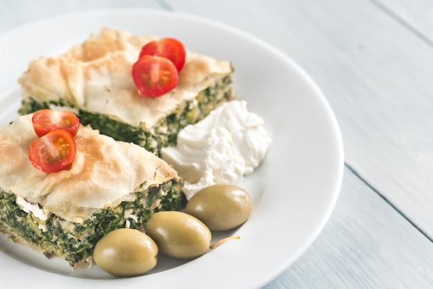 Portion spanakopita - griechischer spinatkuchen auf dem holztisch