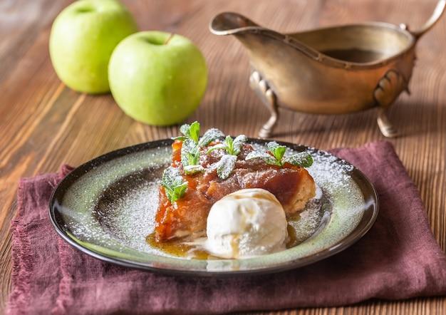 Portion tarte tatin mit frischer minze dekoriert und mit eisbällchen serviert